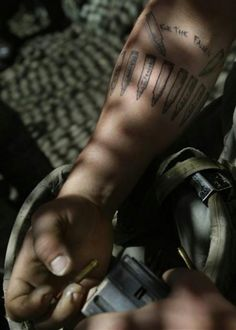 """Staff Sgt. Steven Dubois of Remus, MI and the U.S. Army First Battalion, 26th Infantry loads a rifle magazine with ammunition at firebase Restrepo in the Korengal Valley of Afghanistan's Kunar Province on Monday May 11, 2009. Dubois' tattoo reads """"For The Fallen"""" and lists the names of 17 of his friends who have died in combat during his tours to Iraq and Afghanistan."""
