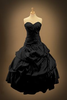This bold Black Gothic Wedding Dress has lacey details and crystal accents. It features a detachable train, and detachable cap sleeve straps. Shown in Black, this gown can also be custom made in red. For other color options, please send me a direct message Available in sizes 0-30
