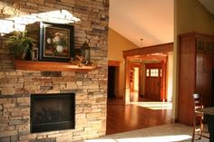 Cultured stone fireplace with craftsman style mantle.