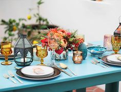 Yellow-gold goblets from Dish Wish, decorative lanterns, and pretty candles tie together this table top look