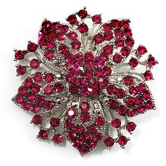 Victorian Corsage Flower Brooch. Featuring a layered flower design, crafted in rhodium plated metal and heavily encrusted with bright magenta coloured crystals. It measures about 5.5cm in diameter and fastens with a flag pin and revolver.