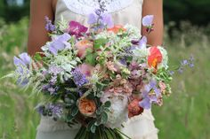 Wild and natural bridal bouquet created from a mixture of peach, pinks, lilac and ivory British flowers, including sweet peas, Poppies, Roses, Cat mint