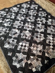 Large throw size black and white quilt made using Riley Blake Tuxedo Collection Charm Packs and Moda Marbled black fabric. Minky was used on the back. Used 32 of the 'X' blocks and 31 of the 16 patch blocks.