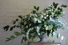 Jennifer Pinder Kent London florist flowers does a botanical themed green and white wedding at Jamies italain restaurant in London threadneedle street with huge amounts of deep green foliage incuding rustic herbs like rosemary and traditional olive branches. White flowers included to add light and brighness. This large, wild urn is perfect for a statement piece or to sit on a pedestal at a church.