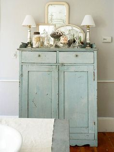 History Lesson | A pale blue-painted storage cabinet in the dining room adds a subtle splash of color without interfering with the room's calming aesthetic. The cabinet's painted surface features characteristic nicks and gashes, which celebrates, rather than masks, the age of the piece.
