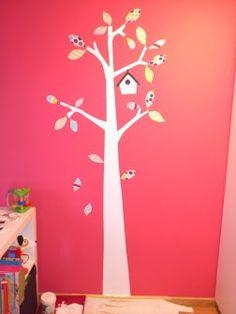 árbol pintado sobre pared y hojas y casa  de retales de papel