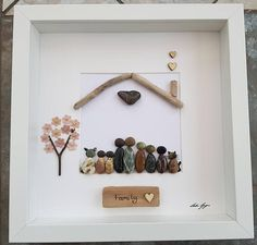 Made to order. Please email me with requirements. A beautiful and unique handmade pebble art picture of Family in home with driftwood roof and chimney, wooden heart embellishments and flowered tree. The picture can be changed to fit your requirements. I can change the number of people and or add an animal. I can also include printed quotes or personalised messages onto picture if required. See images You can order either white or white stained oak effect frames. Please note that there are…
