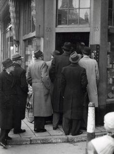 Tweede Wereldoorlog. Mannen in de rij bij een sigarenwinkel. Mogelijk is er tabak te koop. Damrak 85 hoek Zoutsteeg te  Amsterdam, Nederland 29 januari 1942. LET OP! Dit is een hoge resolutie scan die verder niet bewerkt is. Wilt u een bewerkte scan, neem dan contact op met 070-3314160 of verkoop@spaarnestadphoto.nl.