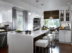 Divine Design - Love modern light pendants, glossy white lacquer island with white modern stools, crisp white cabinets, bamboo roman shades, gray glass tiles, silk gray curtains drapes panels, upholstered window bench with slate gray blue silk pillows, dark wood floors and glass front kitchen cabinets! slate gray blue white brown kitchen colors.