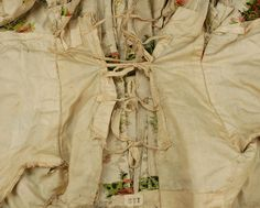 Inside view, robe à la francaise, France, 1774-1793. Cream silk open robe having silver metallic stripe and polychrome silk floral brocade, elbow length sleeve trimmed in knotted net with silk ribbon and tambour embroidered floral applique, neckline, bodice and skirt trimmed in metallic lace and ribbon flowers, self buttons on bodice back for tying up skirt, skirt having front panels appliqued with horizontal bands of net, lace and floral embroidery decorated with red, blue and silver foil…