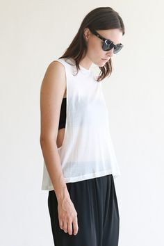 EXPAT-One Size white cotton muscle tee. The EXPAT tee is composed of a soft cotton spandex jersey. The top features open side seams, and contrast black rib crew neck. The loose boy-fit makes this a cool and relaxed go to piece. Made in America