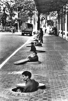During an air raid alert, residents of Hanoi wait in chest-deep sidewalk shelters for the all-clear signal. This photo was taken by by Lee Lockwood, the first American photographer since 1954 permitted to report on daily life in the capital of North Vietnam, 1967.