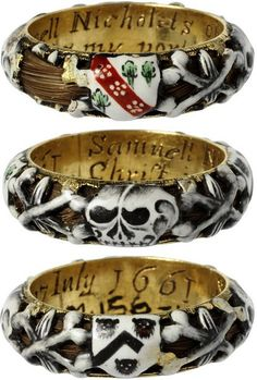 """This enamelled gold mourning ring commemorates the death of Samuel Nicholets of Hertfordshire who died on 7th July 1661, as is recorded in the inscription inside the ring. The ring is hollow, and a lock of hair curls around within it, visible through the openwork of the enamelled decoration of skulls and coats of arms."""""""