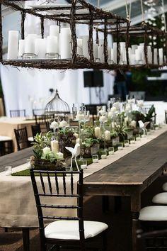 Una decoración de mesas rústicas en jardines para bodas con centros de mesa colgantes hechos con ramas y decorados con velas. El camino central de la mesa luce una cornucopia de velas y follaje sobre una capa de musgo.