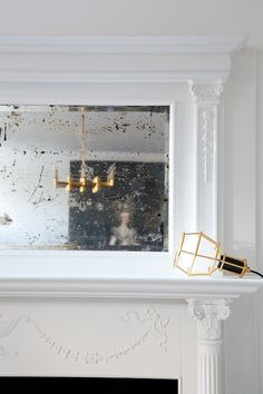 An imperfect mirror keeps a mostly #whitelivingroom from looking too pristine. #mantel #mirror | Photo: Ashley Capp - ashleycapp.com