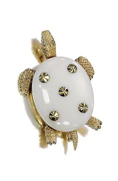 PIN GOLD AND AGATE BY CARTIER   turtle-shaped, the body decorated with an oval cabochon white agate, with five cones of gold for the head, legs and tail, gold engraved to imitatie the turtle skin, eyes accented with rose cut diamonds.