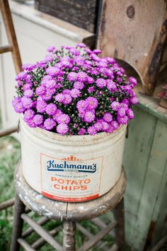 Plant flowers in a repurposed bucket for a rustic display.