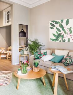 salon y comedor de un piso pequeño con decoracion primaveral en verde y beige y laminas de plantas