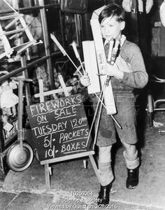 Boy carrying fireworks from a toyshop in Tower Bridge road, 18 October 1949.
