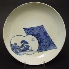 A 17th Century Blue and White Japanese Porcelain Dish, Arita Kilns c.1660-1680. Decorated with a Panel Containing a Scene of a River Landscape with a Rocky Promontory and a Small Boat, this Panel Overlaps a Lozenge Shaped Panel. The Second Panel is Decorated in a Dark Blue Separated from the Lighter Cobalt Blue Background by Sumihajiki, the Subject is of Pine and Bamboo.