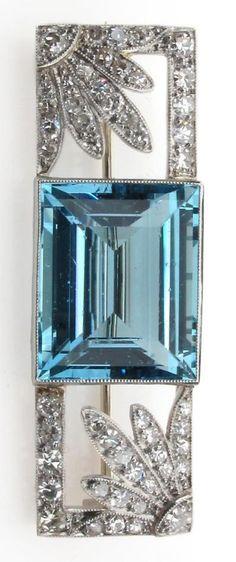 An Art Deco aquamarine and diamond brooch, the baguette shaped aquamarine is millegrain set between two diamond set flower-head sections within rectangular diamond set border.