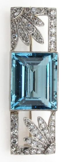 An Art Deco aquamarine and diamond brooch, the baguette shaped aquamarine is millegrain set between two diamond set flower-head sections within rectangular diamond set border. 4cm long. #ArtDeco #brooch
