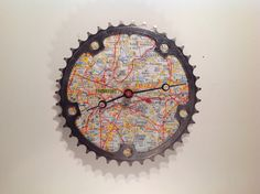 Recycled bicycle parts wall clock- I like the idea of a map behind it