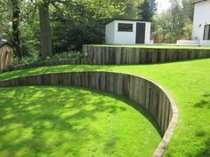 Curved timber retaining wall with vertical railway sleepers, great against a…