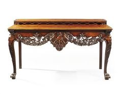 """AN IRISH GEORGE II MAHOGANY SIDE TABLE  CIRCA 1750, MODIFIED CIRCA 1830 WITH CARVING ADDED TO THE SIDES  The moulded rectangular top with a shelf on a raised dotted pierced trellis, the frieze carved with the crest of Creagh of Counties Cork & Clare, & pierced scrolling foliage flowerheads, oak leaves & wheat-sheaves, cabriole legs headed by acanthus masks with claw-and-ball feet, back legs rectangular but apparently original, inscribed 'Geffenes ?' & 'Mrs Jackson'   35½"""" H; 64¼"""" W; 29½"""" D"""