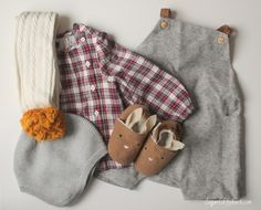 french style baby romper outfit featuring woollen dungarees with suede straps, bunny slippers, gingham asymmetric shirt and knitted baby bonnet with ochre pom pom