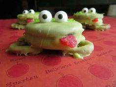 Froggy cookies! Chocolate covered oreos on top of chocolate covered pretzels with a piece of red candy and candy eyes and green sprinkles on the backs