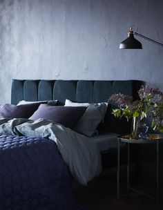 Transformez un cadre de lit MALM de chez IKEA en tête de lit capitonnée. Pour ce projet, nous avons découpé des panneaux de mousse et utilisé un rideau en velours bleu comme garnissage.