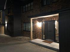 Dark grey cladding with oak column, at night Exterior Lighting, Cladding, Dark Grey, Kitchen Island, Porch, Garage Doors, Kitchens, Mirror, Bathroom