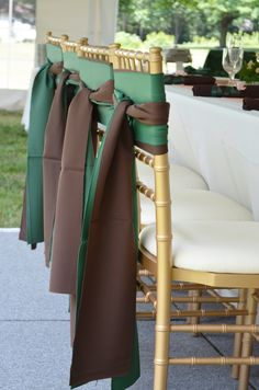 Gold chiavari chairs with green and brown accent sashes