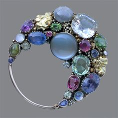 DORRIE NOSSITER 1893-1977  Crescent Brooch   Silver, gold, sapphire, moonstone, green zircon peridot, garnet, chrysoberyl & ruby  Diameter: 5cm (2 in) British, c.1930