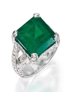 PLATINUM, EMERALD AND DIAMOND RING The emerald-cut emerald weighing 11.08 carats, within an openwork mounting set with round diamonds weighing approximately .70 carat,