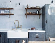 The cabinets and cabinet paint color are both bespoke. A Dowsing & Reynolds Manston Farrier Bronze wall light hangs above the sink - Dorset Cottage Project