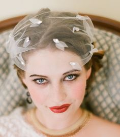 Stunning mix between a cap and birdcage veil — complete with scattered clusters of hand-cut, chiffon petals and marquis-shaped, claw-set rhinestones.