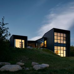 Canadian studio Alain Carle Architecte has embedded a black, sculptural dwelling into a sloped site overlooking the St Lawrence River. Called La Charbonnière, the home is part of a housing development on a mountainside in Cap à L'Aigle, a resort village in Quebec's Charlevoix region. The site had been cleared by the developer to provide views