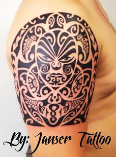 MAORI: Detailed arm piece. Face in middle of tattoo. Dark, bold colouring.