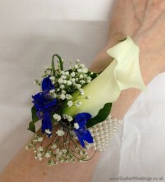 White calla lily, blue delphinium and gypsy grass wrist corsage on a pearl bracelet  Wedding Flowers Liverpool, Merseyside, Bridal Florist, Booker Flowers and Gifts, Booker Weddings