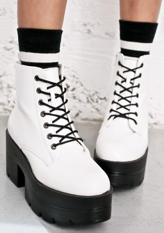 """Easy Ryder Platform Boots are gonna be yer ride or die out on da road. These work boots get a sassy update with a dope white colored vegan leather construction and contrasting black 3.5"""" heels, 2"""" platforms and front lace closure."""