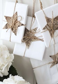 Crisp and organic: bark paper stars on white wrapping paper, tied with twine.