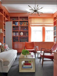 Coral lacquered walls (wow!) - mid century orange leather chairs and light fixture