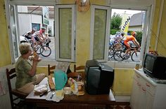 With her kitchen window providing a front-row view, a woman in Caen takes in the fifth stage of the Tour de France.
