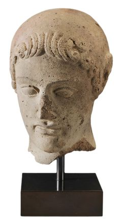 Ancient Terracotta Head of a Youth - Lot 438 of September 2012 Auction -   Etruscan, 5th century BC, after a Greek prototype, colored gray with red terracotta showing through in hair, 8 x 5-1/2 x 7-1/4 in., supported by metal rod extending up from modern black base - Estimate $3,000 to $5,000.