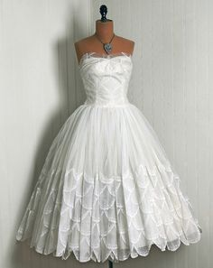 Elegant 1950's ivory-white French Chantilly lace dress. Pleated sheer tulle, seductive low-cut plunge sweetheart fully-boned strapless bodice, cocktail length, sculpted scalloped petals, princess full circle skirt. by Cahill, Beverly Hills.