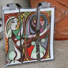 Tote bag made from clear vinyl, with pockets to hold and change out artwork (currently holds PIcasso).