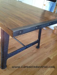 I like the use of angle iron edging the lumber. Detail of reclaimed bowling alley wood top table, steel angle iron end caps, vintage cast iron machine base legs. Made by Carbon Industrial Design.