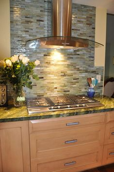Glass tile backsplash green blue shiny, w/oak yellow wall.  This should be the focal point of the kitchen area.May need one with a speck of darkness.